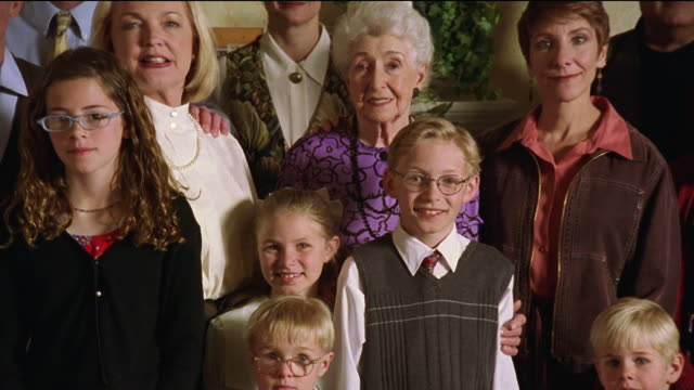 medium shot zoom out multi-generational family posing for a group photo indoors with one boy fidgeting - large family stock videos and b-roll footage