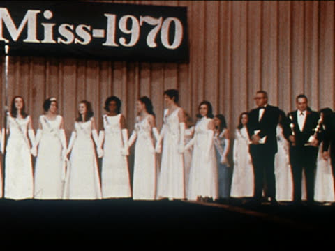 1970 medium shot zoom out pan jr miss 1970 contestants on stage in long white dresses holding hands - formal glove stock videos and b-roll footage