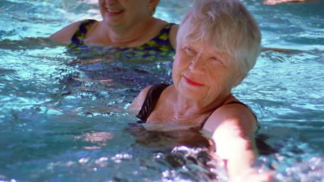 vídeos de stock, filmes e b-roll de medium shot zoom out pan seniors in swimming pool doing exercises - medium group of people