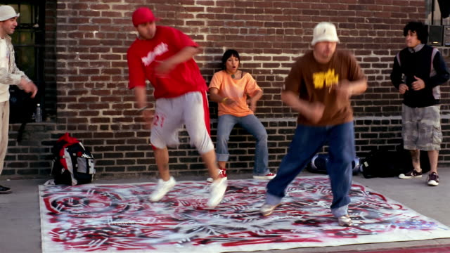 stockvideo's en b-roll-footage met medium shot zoom out pan two men breakdancing on graffiti surface/ young woman dancing / los angeles, calfornia - hiphop