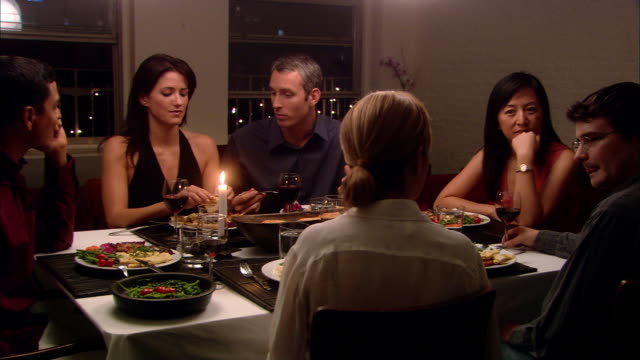 medium shot zoom out people eating and talking during dinner party - evening meal stock videos & royalty-free footage