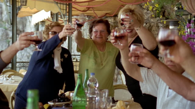 medium shot zoom out people raising glasses of red wine and toasting at celebration / praiano, amalfi coast, italy - italien stock-videos und b-roll-filmmaterial