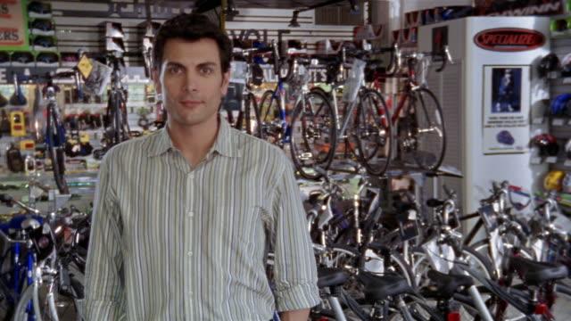 vídeos y material grabado en eventos de stock de medium shot zoom out portrait of man standing in front of rack of bicycles at bike shop / zoom in man smiling at cam - un solo hombre de mediana edad