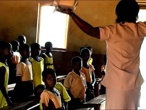 Medium shot zoom out schoolchildren standing at attention as teacher speaks/ Ghana