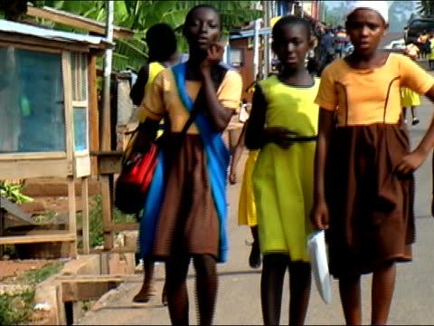 Medium shot zoom out schoolchildren walking home/ Ghana