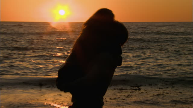medium shot zoom out silhouette of man picking woman up and kissing her on beach at sunset/ monterey county, california - ragged point stock videos and b-roll footage