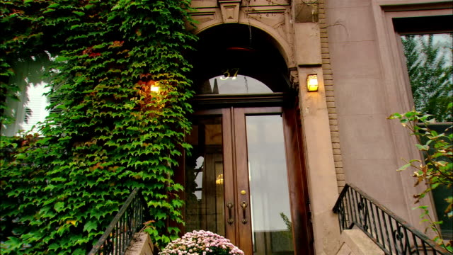 Medium shot zoom out stoop of ivy covered brownstone building/ Brooklyn, New York