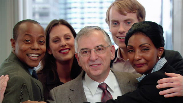 medium shot zoom out team of office workers hugging manager and looking at camera/ zoom out people getting out of huddle/ new york, new york - admiration stock videos & royalty-free footage