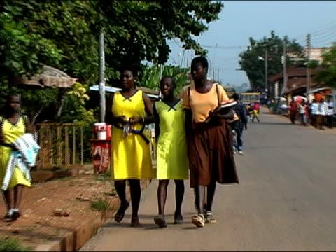 Medium shot zoom out teenagers walking home from school/ Ghana