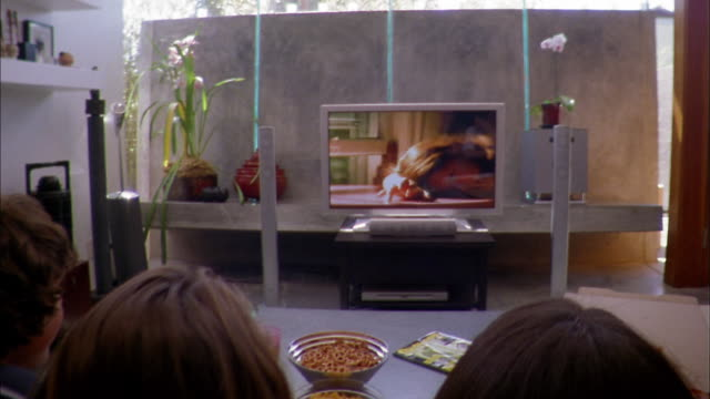 Medium shot zoom out teenagers watching video on flat widescreen TV in living room