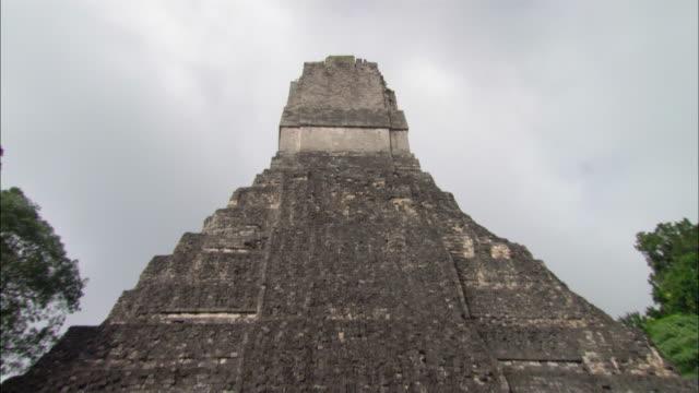 vidéos et rushes de medium shot zoom out temple of the grand jaguar at the great plaza mayan ruins / tikal, guatemala - temple