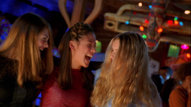 vídeos de stock, filmes e b-roll de medium shot zoom out three teen girls posing arm-in-arm at party and laughing with people dancing in background - de braços dados