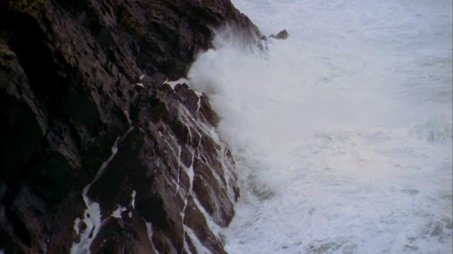 medium shot zoom out waves crashing into rock cliffs / croagh patrick, ireland - 2002 stock videos & royalty-free footage