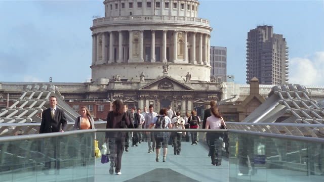 medium shot zoom out wide shot pedestrians on millennium bridge over thames with view of dome of st paul's cathedral/ london - london millennium footbridge stock videos & royalty-free footage