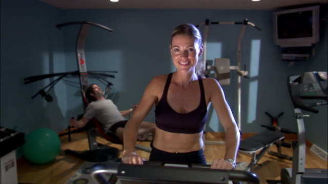 medium shot zoom out woman riding stationary bike in exercise room as man works out in background/ green bay, wisconsin - exercise room stock videos & royalty-free footage