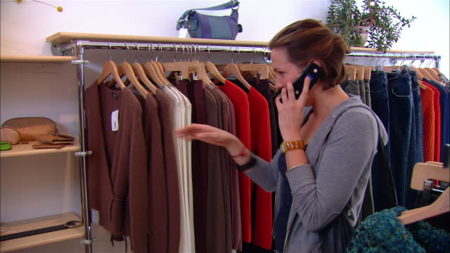 Medium shot zoom out young woman answering mobile phone while shopping in clothing store/ taking sweater off rack and looking at it while talking/ Westfield, New Jersey