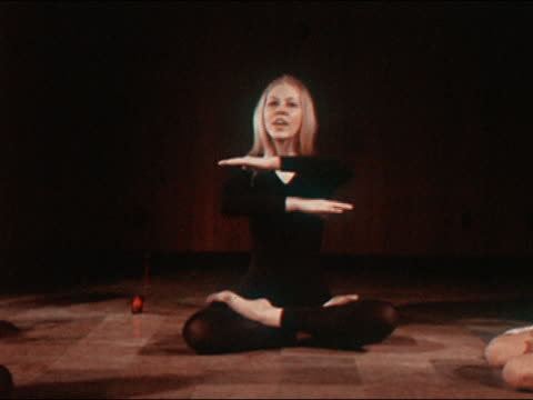 1970 medium shot zoom out young woman in leotard sitting in lotus position and teaching yoga class