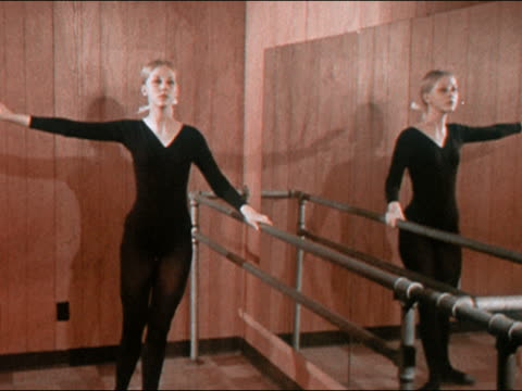 1970 medium shot zoom out young woman wearing leotard practicing ballet moves at barre in front of mirror