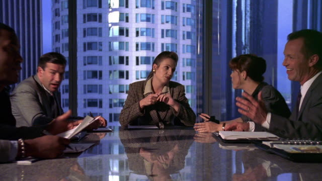 Medium shot zoom out zoom in businesswoman talking to other executives at conference table during meeting