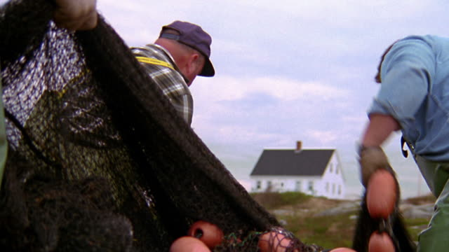 medium shot zoom out zoom in profile 3 fishermen in hats pulling fishing nets into big pile / house in background / nova scotia - nova scotia stock videos & royalty-free footage