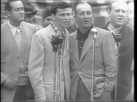 medium shots of bing crosby singing with frank sinatra as audience yells for more singing / shot of bob hope interrupting with a joke / shot of... - ボブ ホープ点の映像素材/bロール