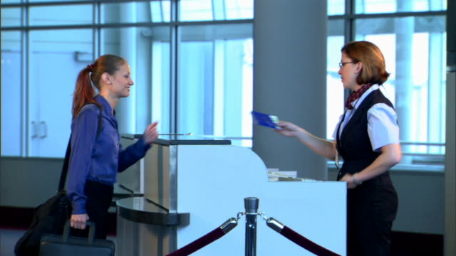 medium side view of a businesswoman getting her ticket checked by a flight attendant at the gait. - airline check in attendant stock videos and b-roll footage