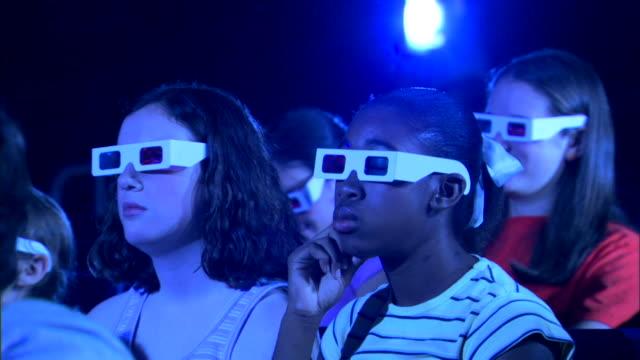 medium side view of a group of people watching a 3d movie. - biosalong bildbanksvideor och videomaterial från bakom kulisserna