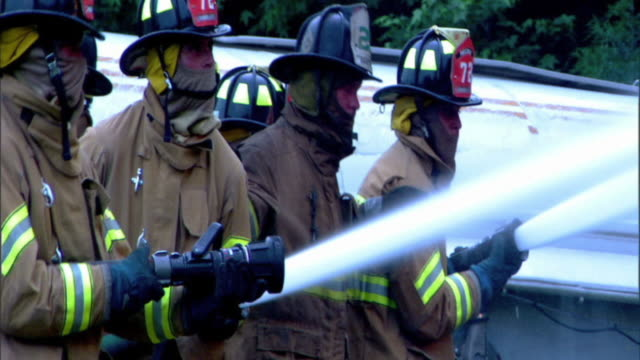 medium side view of firefighters working together with hoses to spray water on an unseen fire. - vigile del fuoco video stock e b–roll