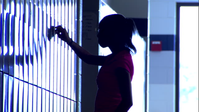 Medium silhouette of a student opening her locker and getting a book.