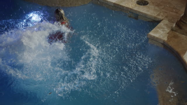 Medium slow motion high angle shot of man jumping in pool / Cedar Hills, Utah, United States