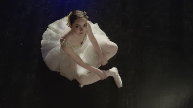 vídeos y material grabado en eventos de stock de medium slow motion high angle shot of smiling ballerina sitting on floor / salt lake city, utah, united states - tutú