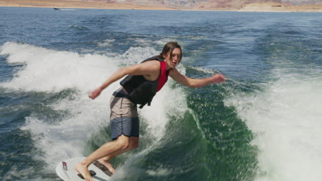 vídeos y material grabado en eventos de stock de medium slow motion high angle shot of wake surfer doing tricks / lake powell, utah, united states - pantalón corto