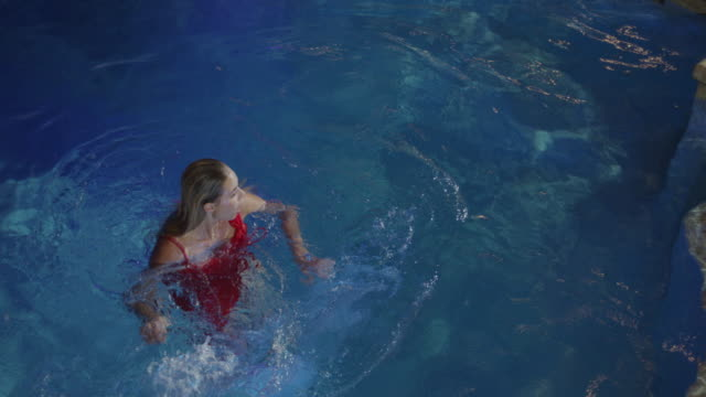 Medium slow motion high angle shot of woman in dress floating in pool / Cedar Hills, Utah, United States