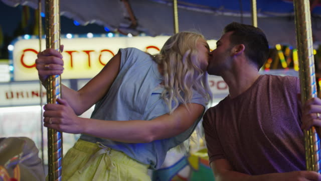vidéos et rushes de medium slow motion low angle shot of couple kissing on carousel / pleasant grove, utah, united states - embrasser sur la bouche