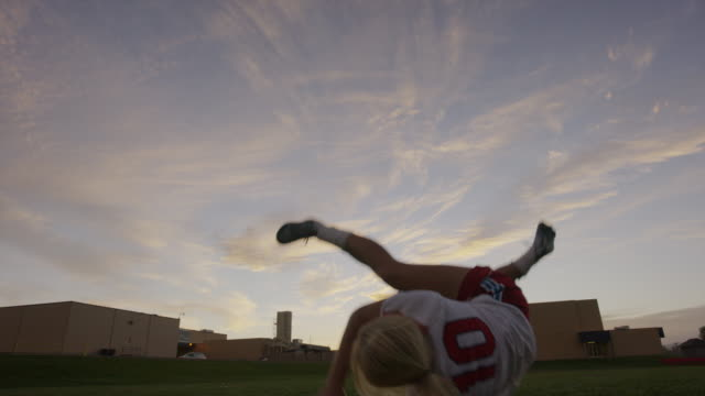 Medium slow motion low angle shot of girl practicing bicycle kick / Springville, Utah, United States