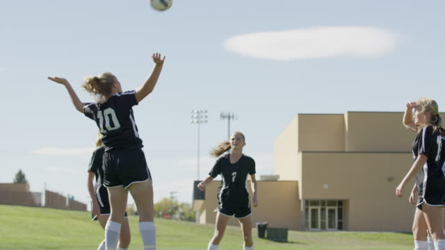 medium slow motion low angle shot of soccer players practicing keepie uppie / springville, utah, united states - five people stock videos and b-roll footage