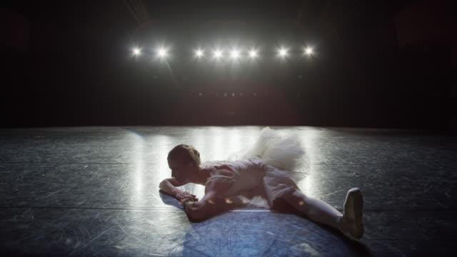 medium slow motion panning shot of ballerina doing splits on stage / salt lake city, utah, united states - balletttänzer stock-videos und b-roll-filmmaterial