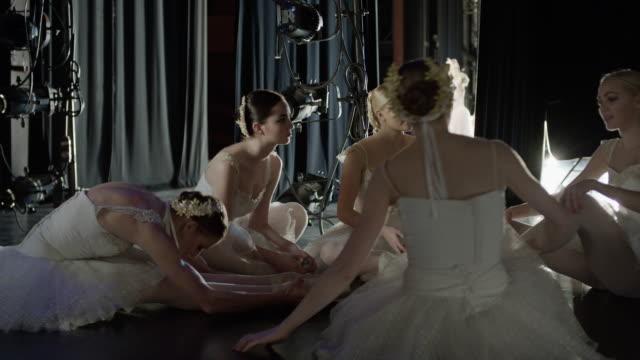 medium slow motion panning shot of ballerinas stretching backstage / salt lake city, utah, united states - backstage stock videos & royalty-free footage