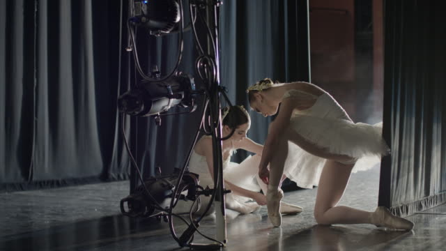 medium slow motion panning shot of ballerinas tying shoes backstage / salt lake city, utah, united states - ballet shoe stock videos and b-roll footage