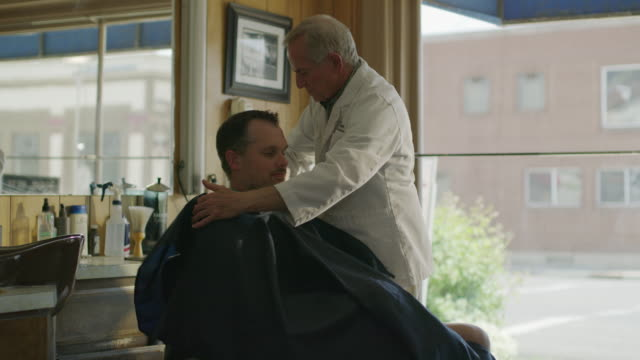 medium slow motion panning shot of barber putting smock on customer / pleasant grove, utah, united states - barber stock videos & royalty-free footage