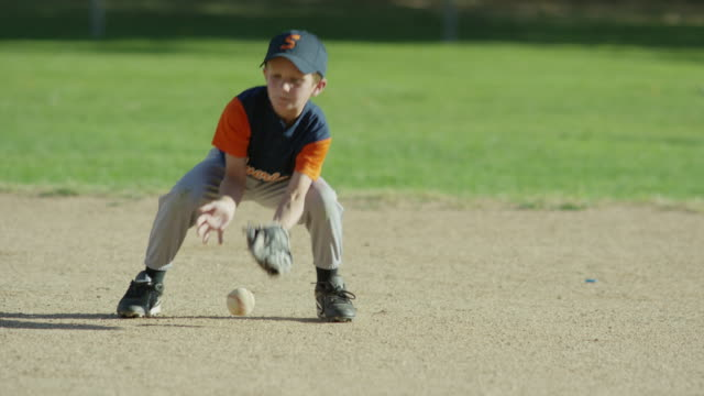Medium slow motion panning shot of baseball infielder fielding ball / American Fork, Utah, United States