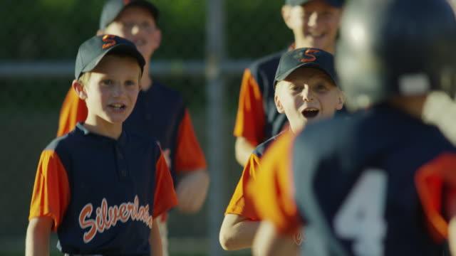 medium slow motion panning shot of baseball team celebrating / american fork, utah, united states - baseballmannschaft stock-videos und b-roll-filmmaterial