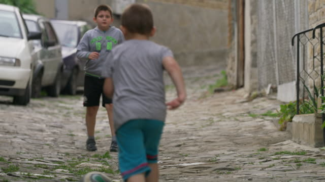 Medium slow motion panning shot of children playing street soccer / Veliko Tarnovo, Bulgaria