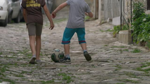 medium slow motion panning shot of children playing street soccer / veliko tarnovo, bulgaria - bulgaria stock videos & royalty-free footage
