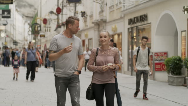 Medium slow motion panning shot of couple eating ice cream in busy street / Salzburg, Austria