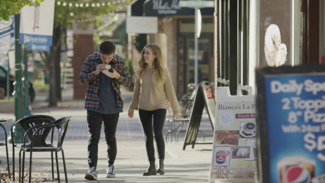 medium slow motion panning shot of couple on sidewalk sharing pastry / provo, utah, united states - provo stock videos & royalty-free footage