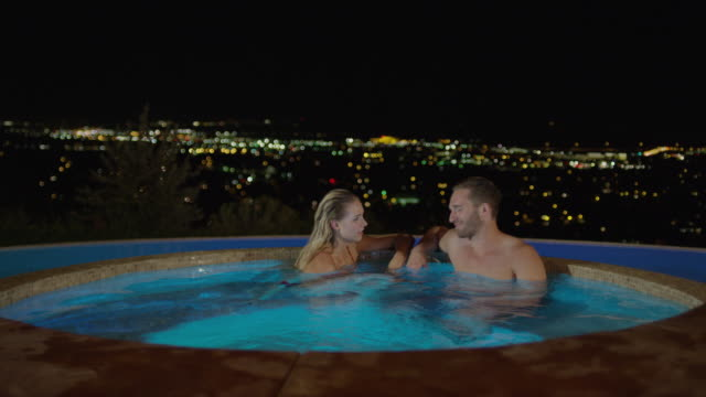 Medium slow motion panning shot of couple relaxing in hot tub / Cedar Hills, Utah, United States