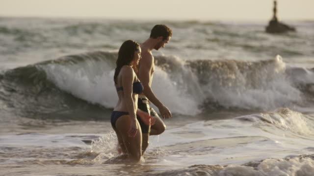 medium slow motion panning shot of couple walking in ocean / esterillos, puntarenas, costa rica - badbyxor bildbanksvideor och videomaterial från bakom kulisserna