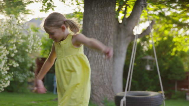 medium slow motion panning shot of girl dancing in yard / springville, utah, united states - springville utah stock videos & royalty-free footage