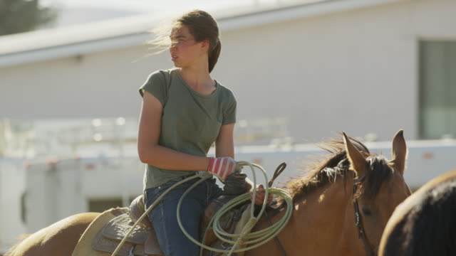 vídeos de stock, filmes e b-roll de medium slow motion panning shot of girl on horse holding lasso / lehi, utah, united states - lehi